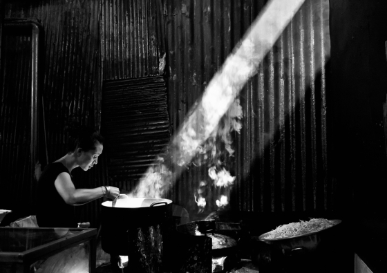 Cambodian woman cooks by natural light.
